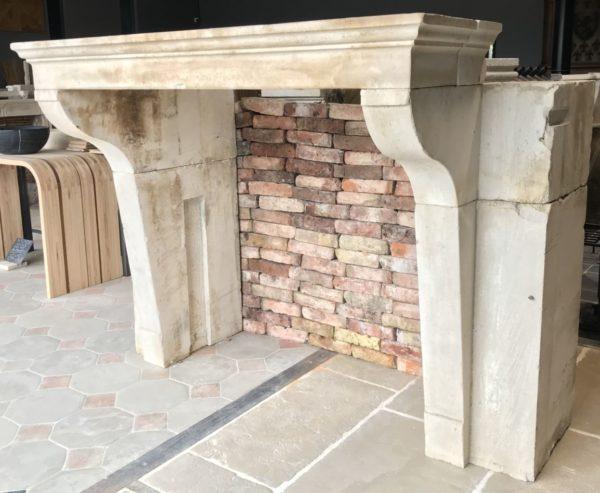 cheminee campagnard devant un mur de brique ancienne