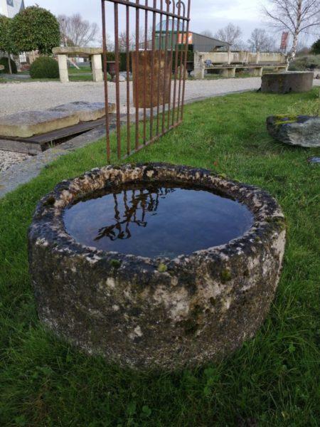 auge ronde remplit d'eau en pierre calcaire