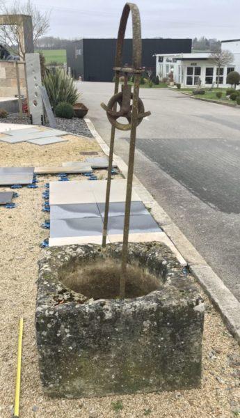 puits en forme carré sculpté dans un bloc ancien